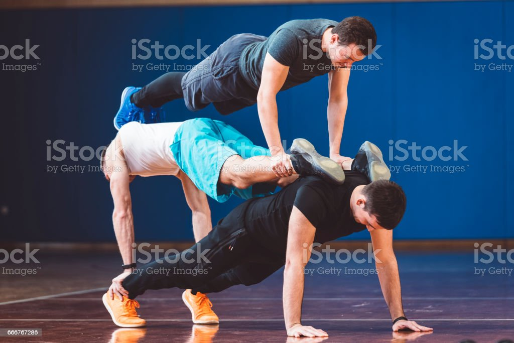 Three young people doing balance exercises in the gym stock photo