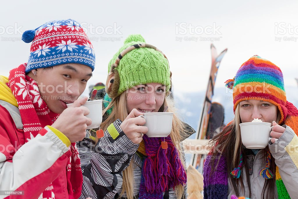 Three young people drinking capuccino outdoors in ski area stock photo