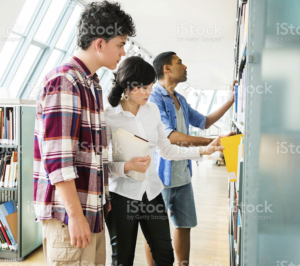 Three young people in library royalty-free stock photo