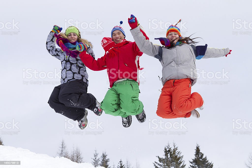 Three young people in multi colored clothes jumping on snow royalty-free stock photo