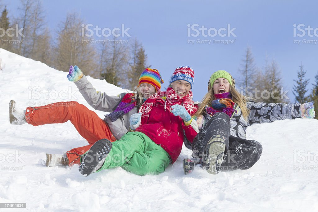 Three young people in winter clothes falling downhill on snow royalty-free stock photo