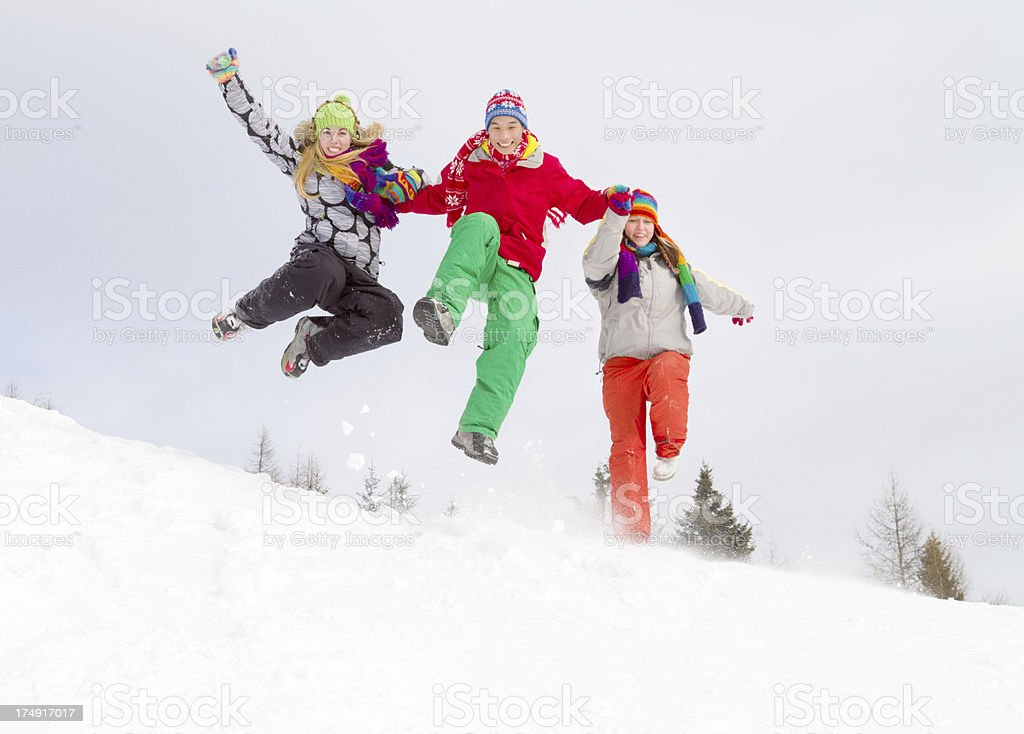 Three young people in winter clothes jumping downhill on snow royalty-free stock photo