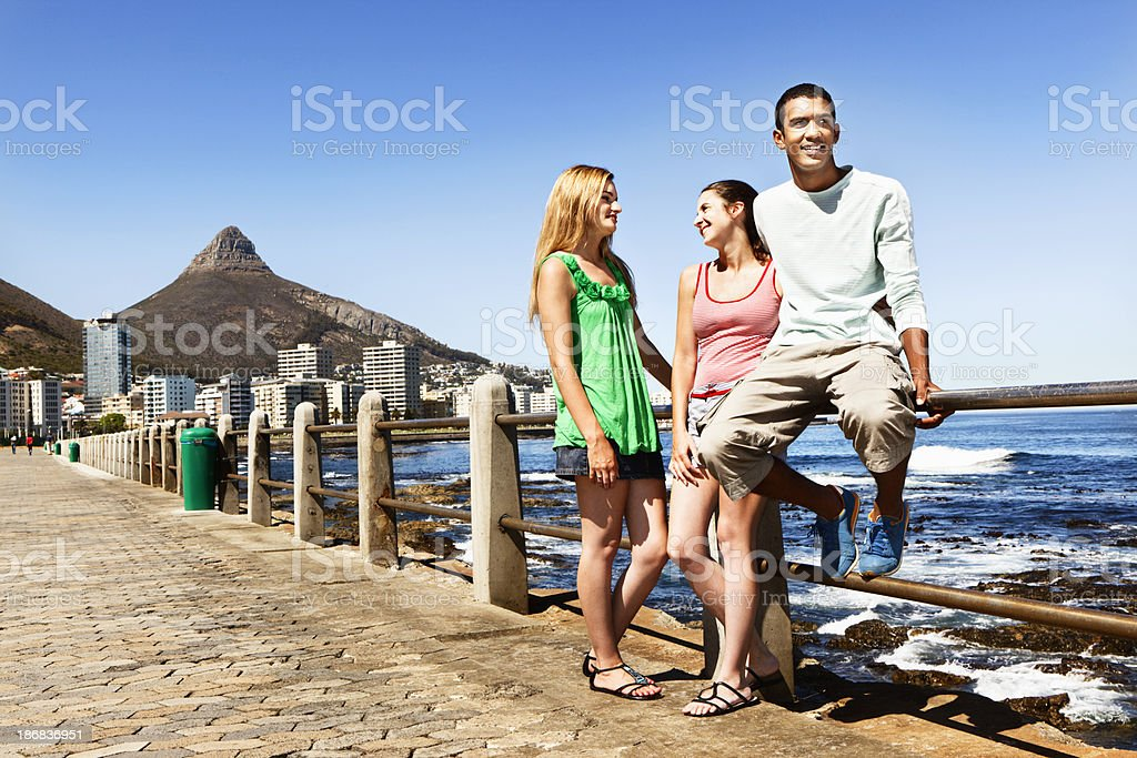 Three young people lean on railings at water's edge royalty-free stock photo