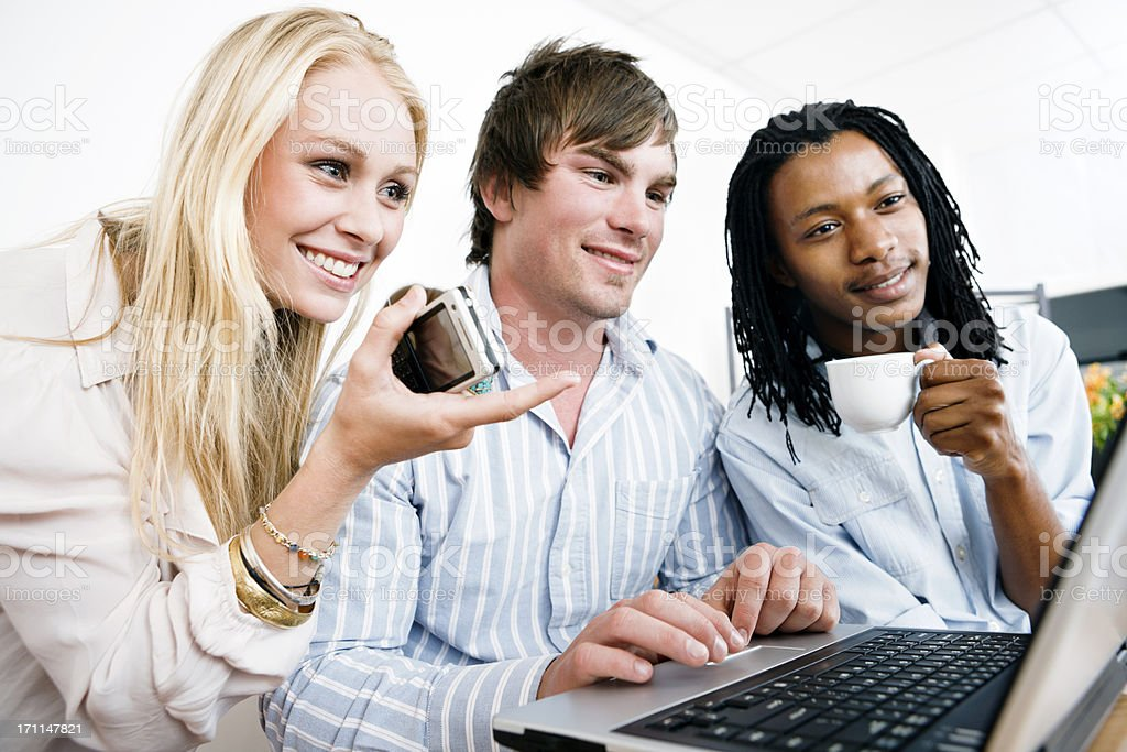 Three young people looking at laptop and drinking coffee royalty-free stock photo