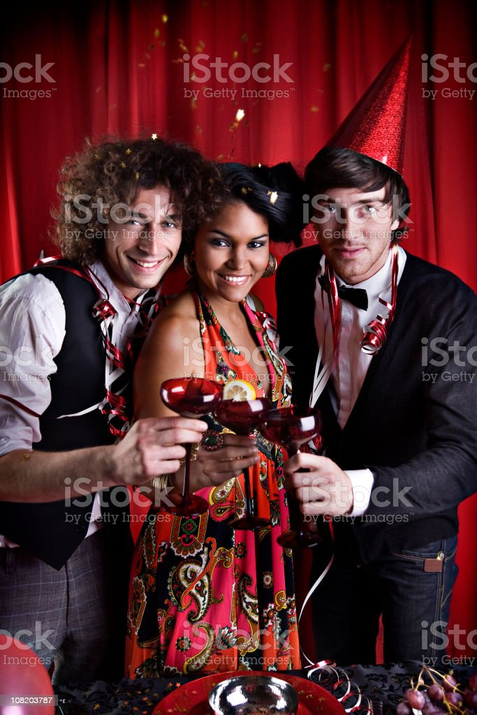 Three Young People Making Toast with Drinks at Party royalty-free stock photo