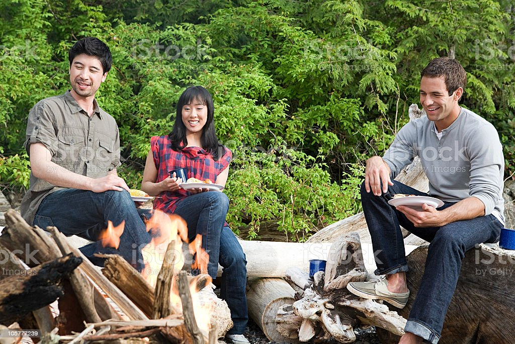Three young people sitting around campfire royalty-free stock photo