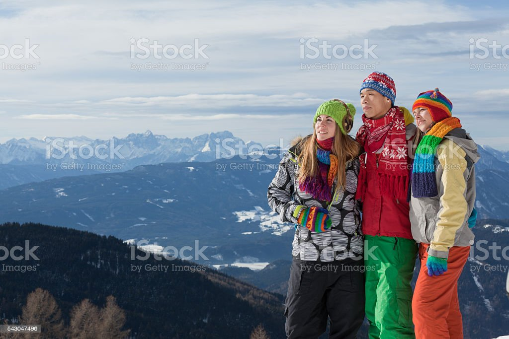 Three young people standing on mountain peak in winter stock photo