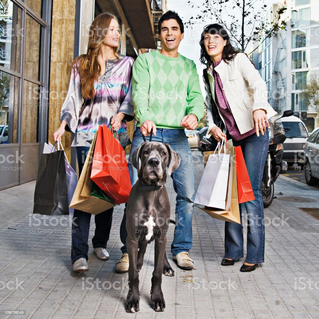 Three Young People Walking Dog and Holding Shopping Bags royalty-free stock photo