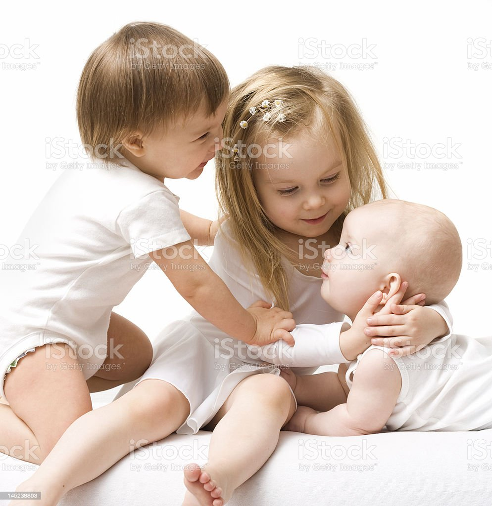 Three young siblings playing together royalty-free stock photo