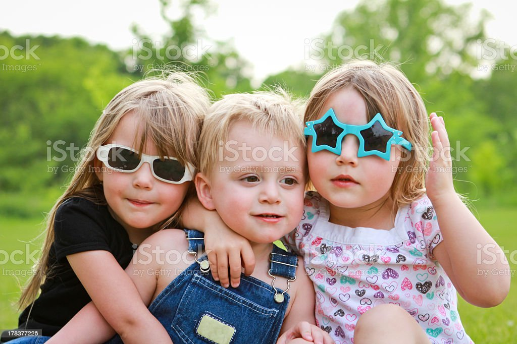 Three young siblings sitting outside in the sun stock photo