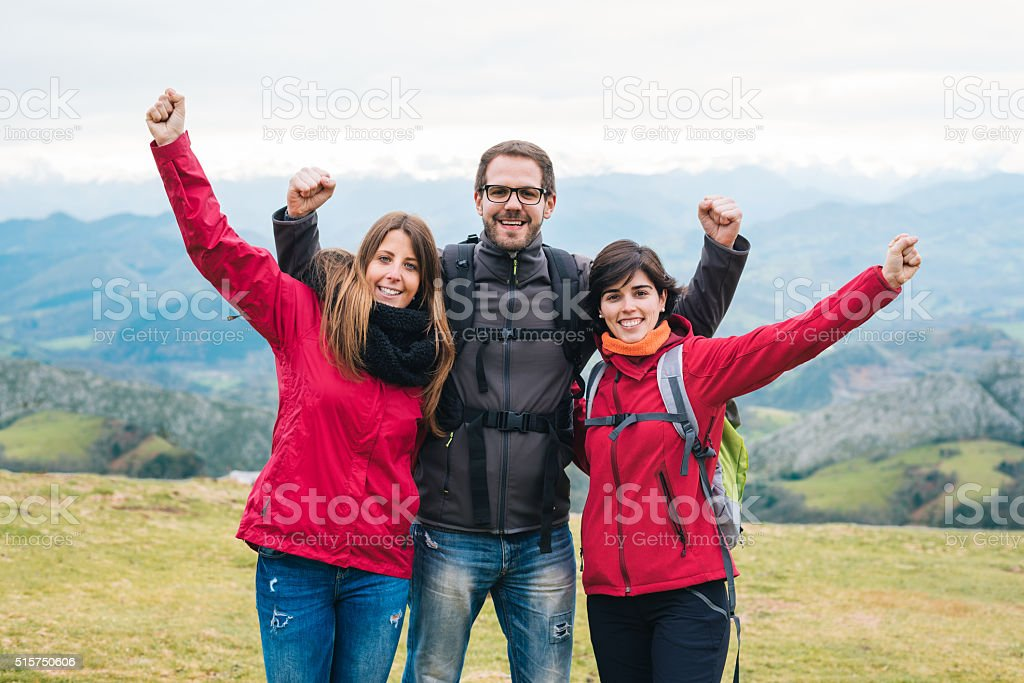three young smiling friends hiking outside embracing and fists up stock photo
