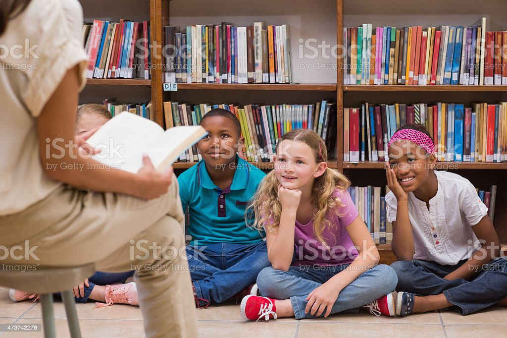 Three young students listening to a story in the library stock photo