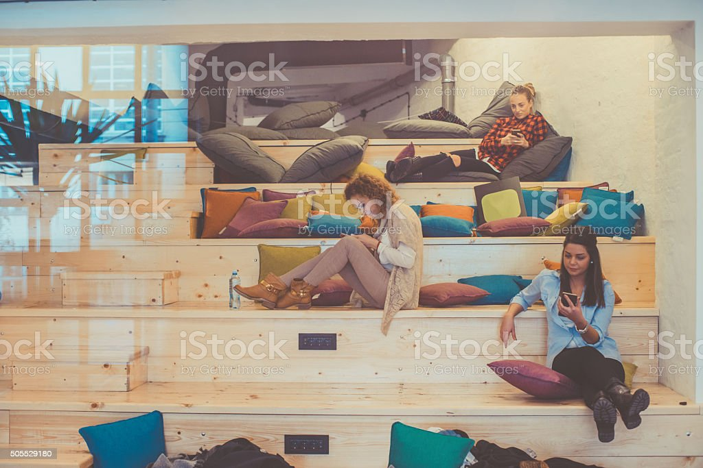 three young woman realxing at the office lounge area stock photo