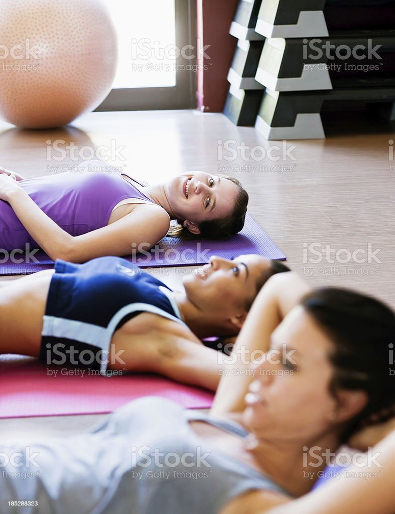 Three young women doing sit ups in gym stock photo