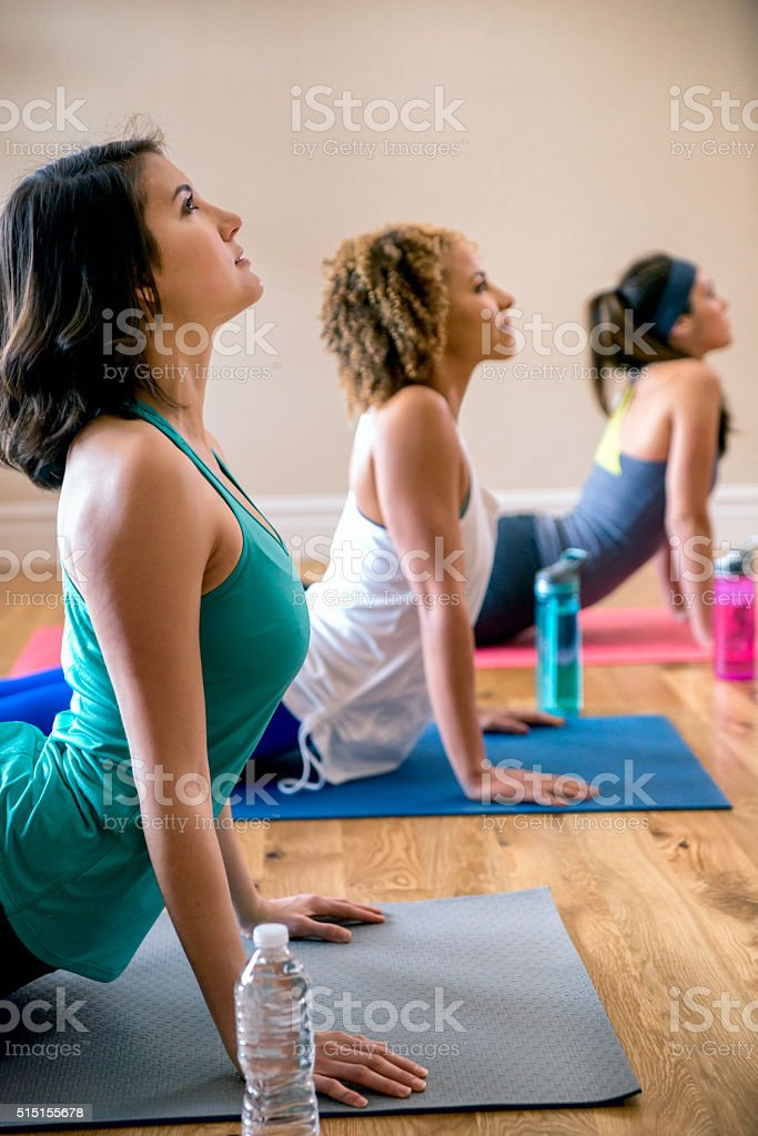 Three Young Women Doing Yoga Cobra Pose stock photo