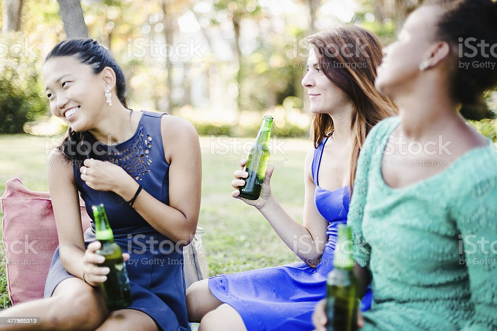 Three young women drinking beer at the park royalty-free stock photo