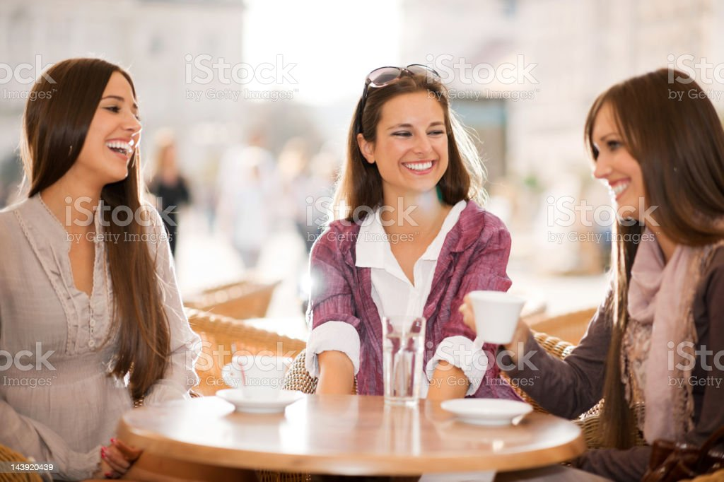 Three young women drinking coffee in a cafe. royalty-free stock photo