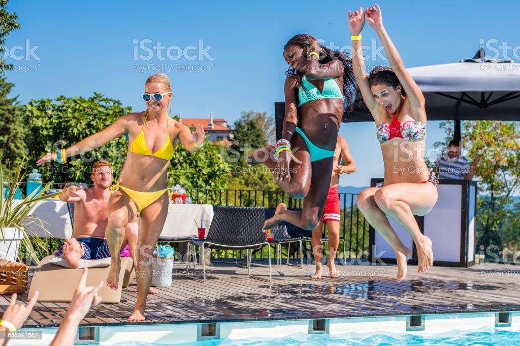 Three young women in bikini jumping into pool stock photo