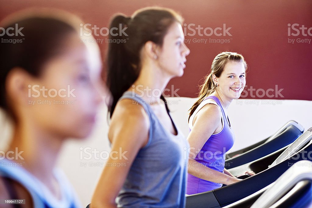Three young women on exercise bikes one smiling at camera stock photo