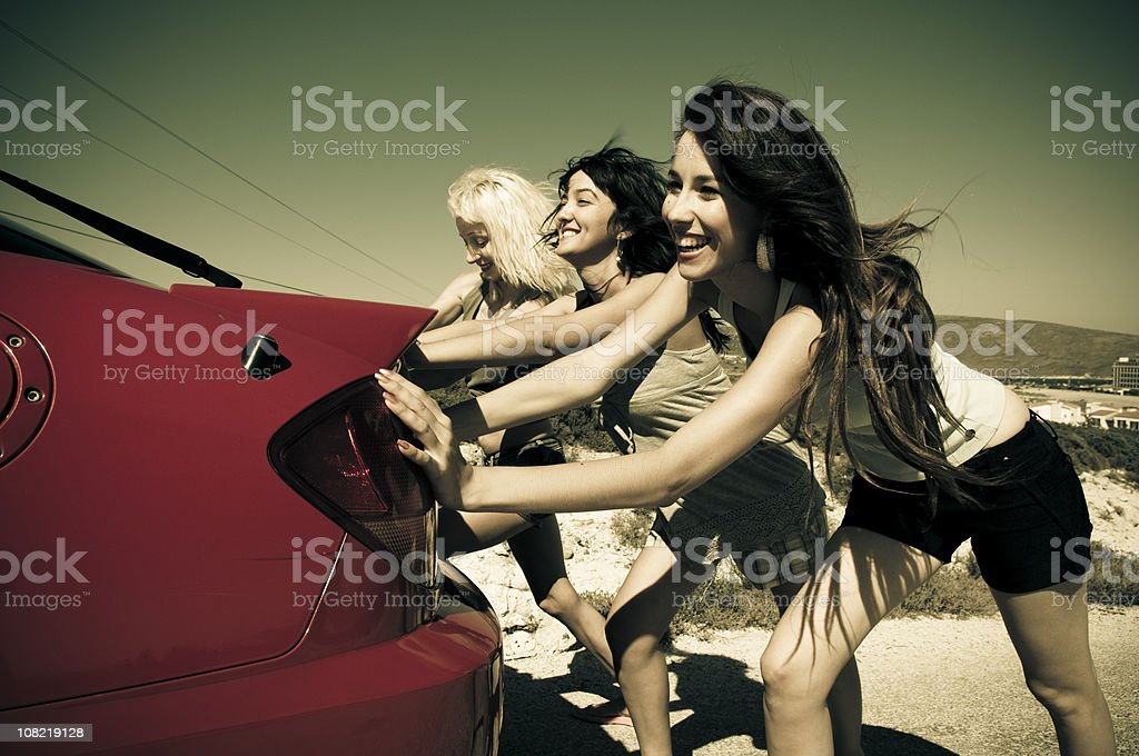 Three Young Women Pushing Red Car Along Road royalty-free stock photo