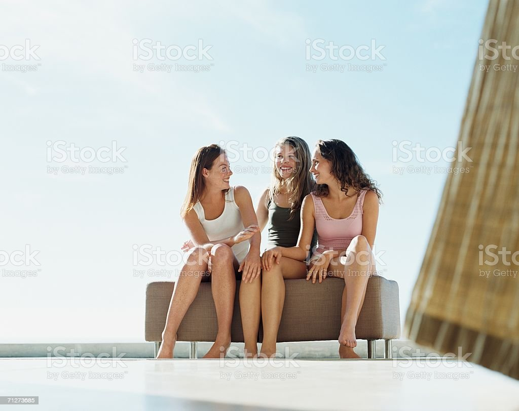 Three young women sat outside stock photo
