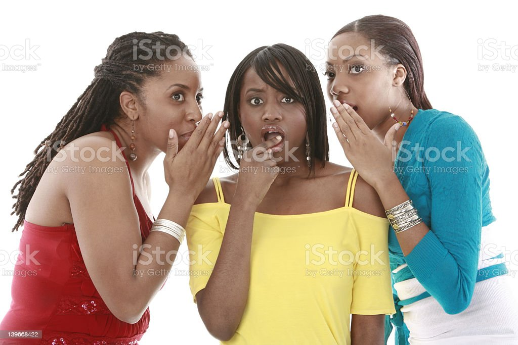 Three young women sharing secrets on a white background stock photo