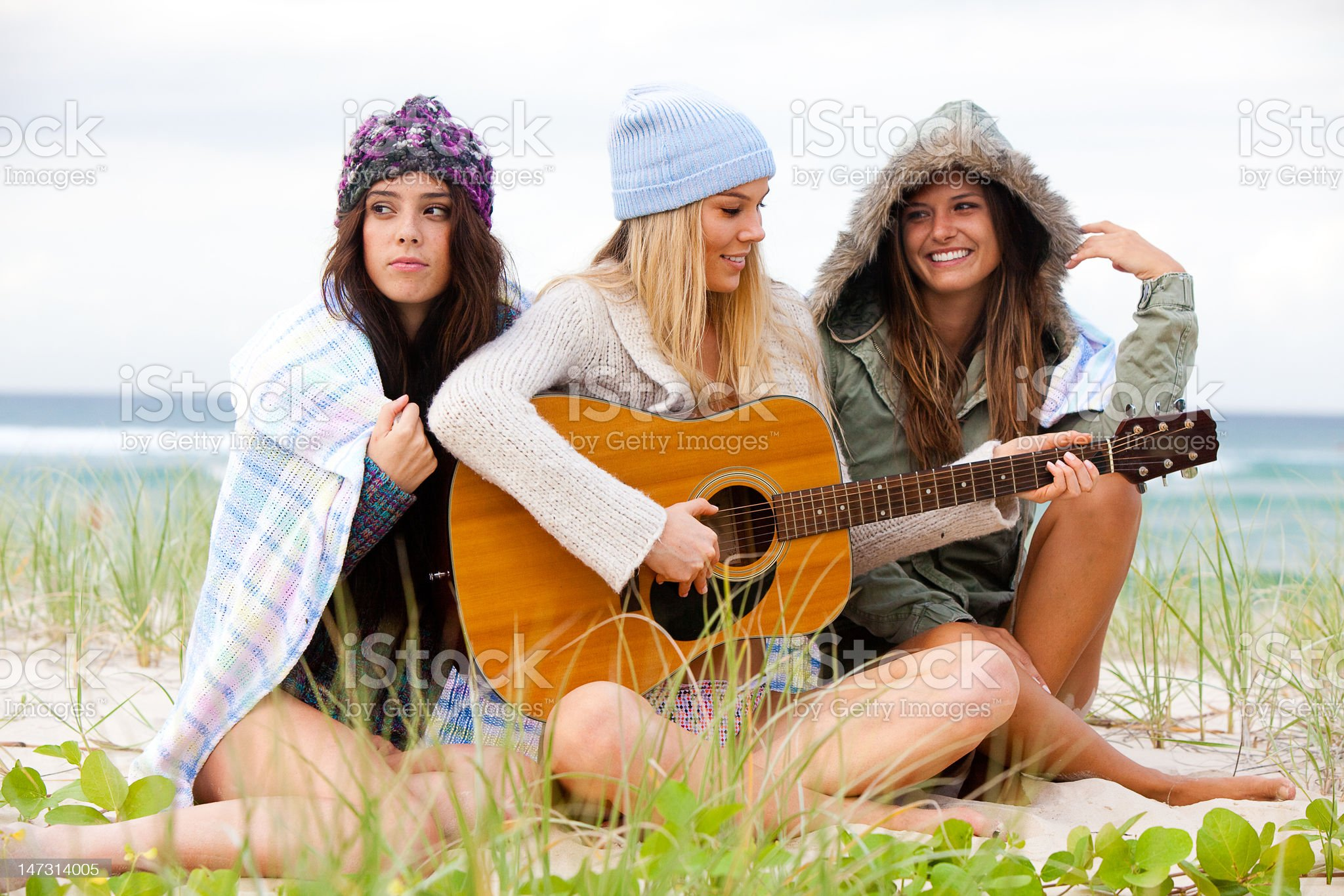 Three Young Women Sitting on Chilly Beach With Guitar royalty-free stock photo