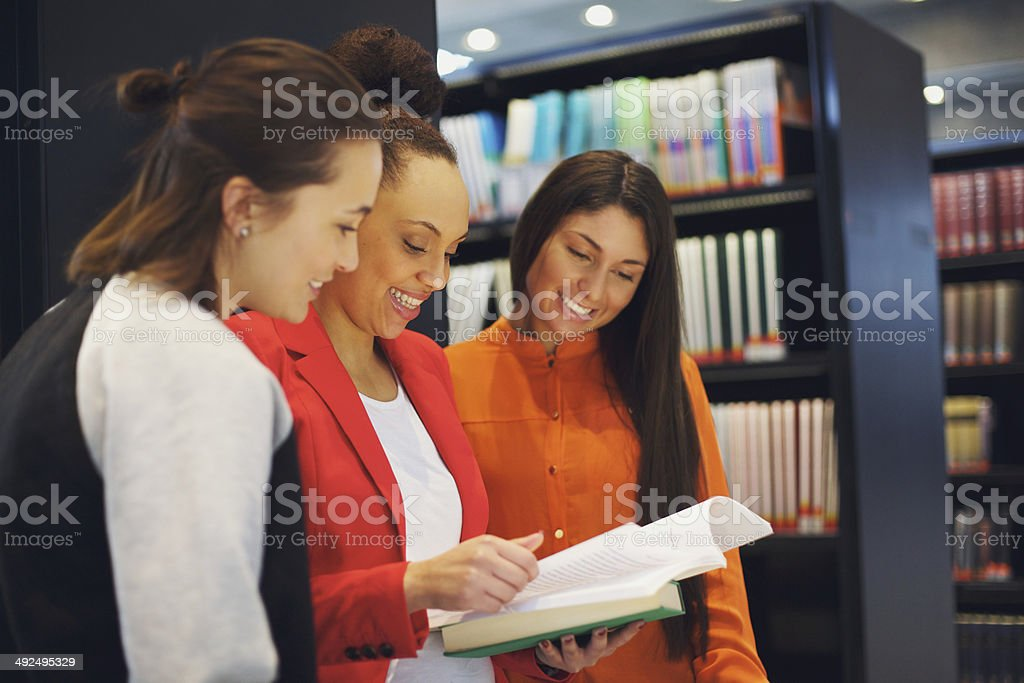 Three young women students standing in library stock photo