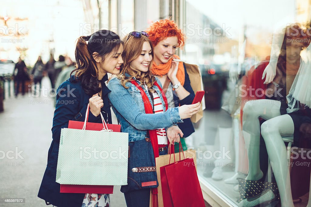 Three young women taking images while window shopping stock photo