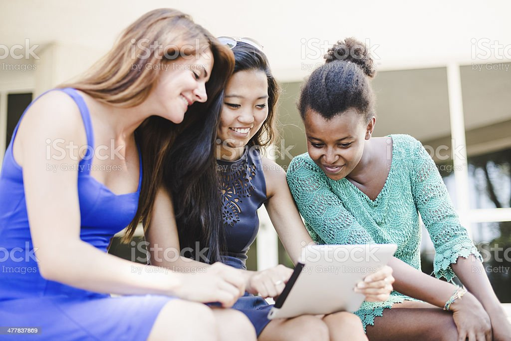 Three young women using a digital tablet royalty-free stock photo