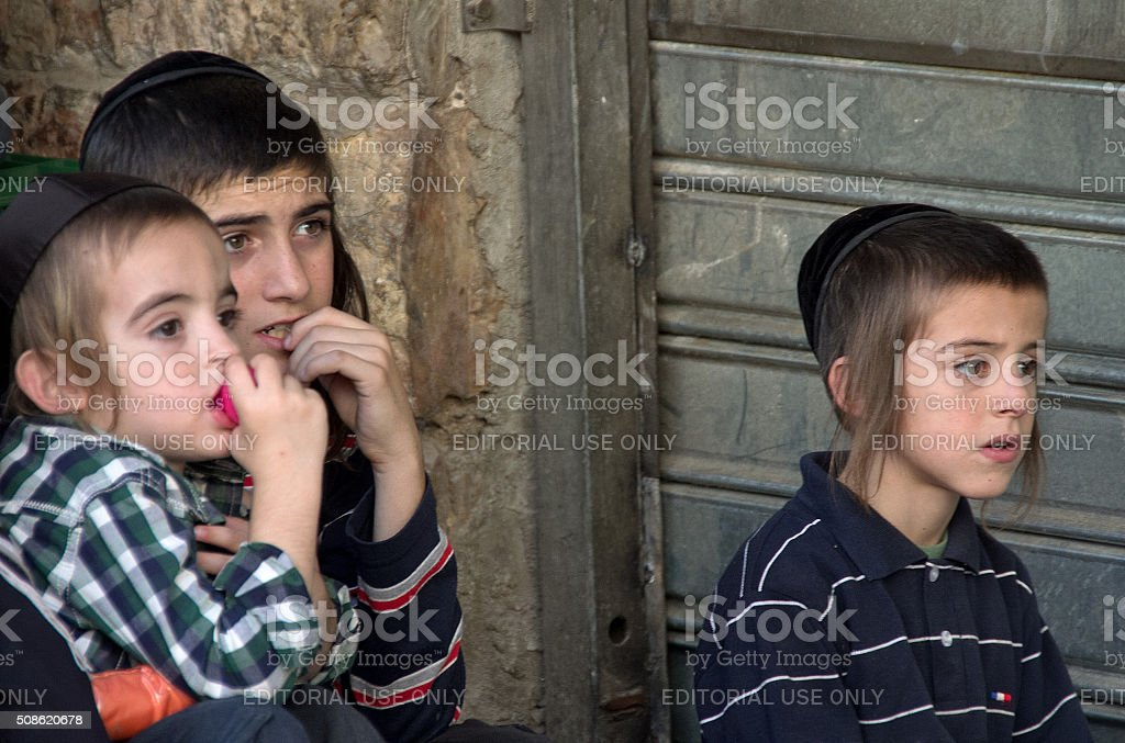 three youngsters observe events at a market stock photo