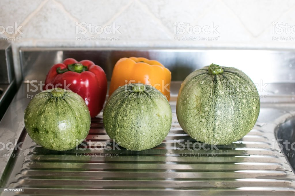 Three zucchini and two peppers stock photo