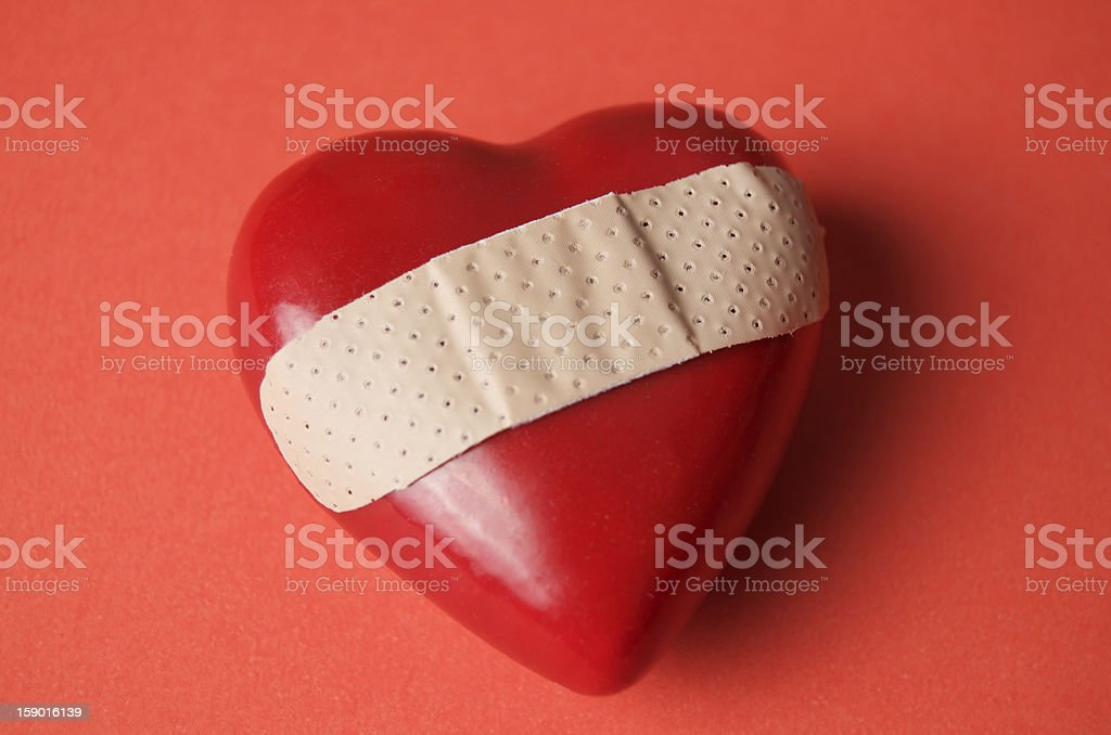 Three-dimensional heart with Band-Aid on red surface stock photo