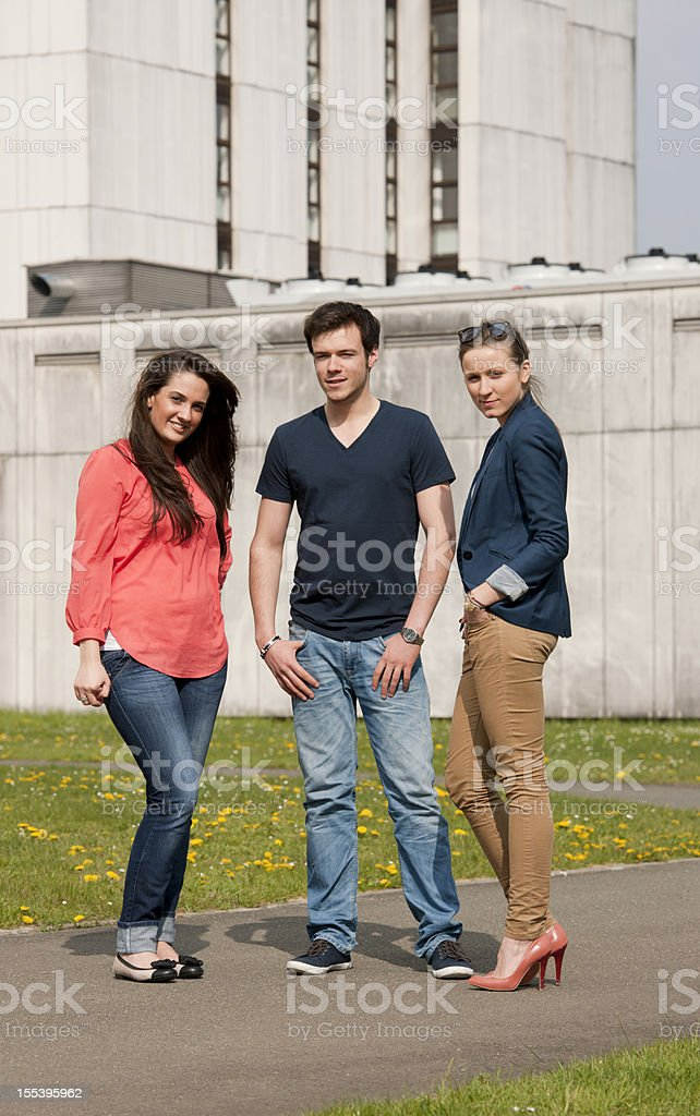 Threee young people in front of university stock photo