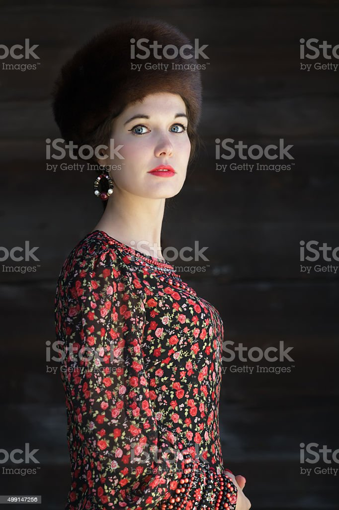 Three-quarter view portrait of young woman with fur Cossack hat stock photo