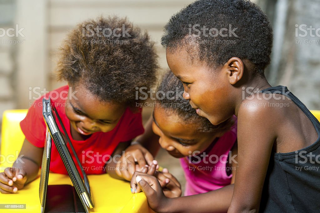 Threesome african kids having fun with tablet. stock photo