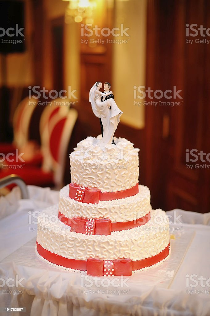 three-tiered white wedding cake with red ribbons royalty-free stock photo