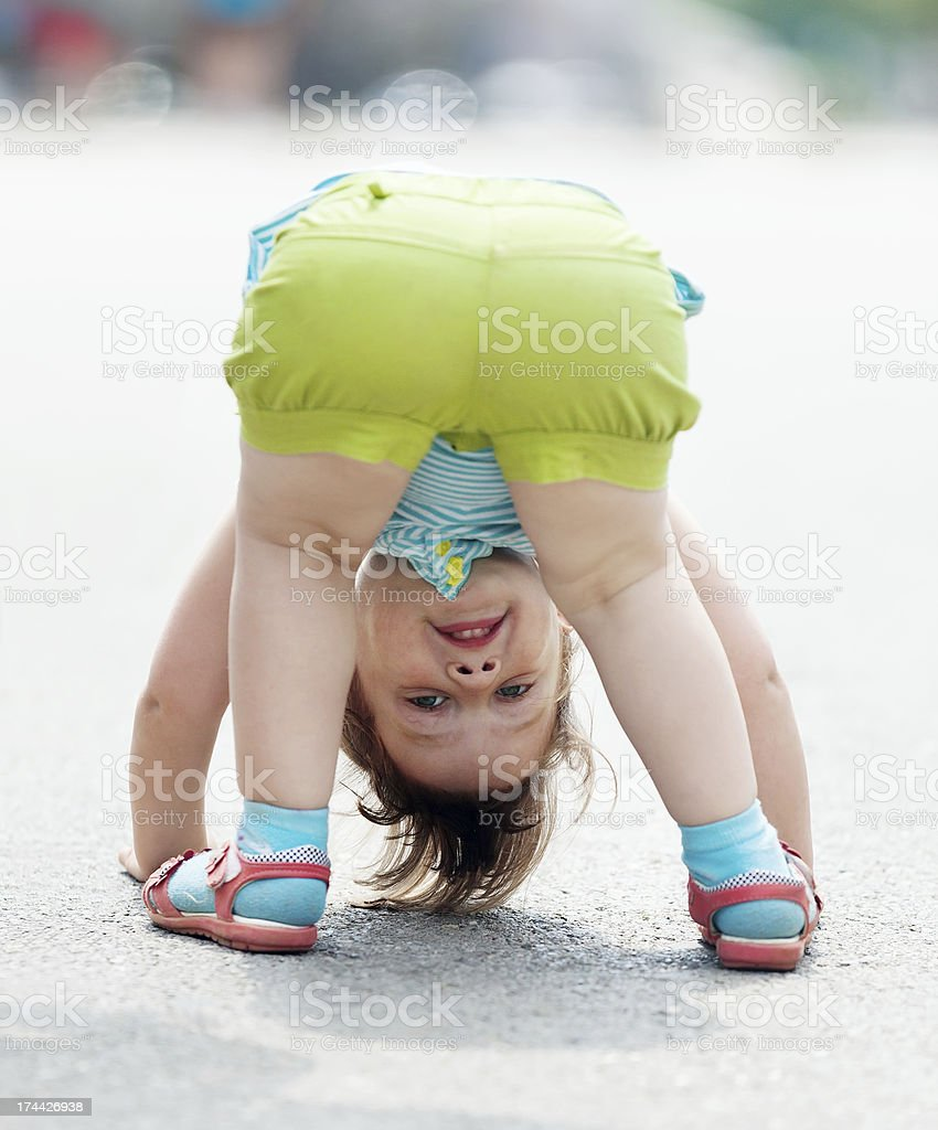 three-year baby girl playing upside down royalty-free stock photo