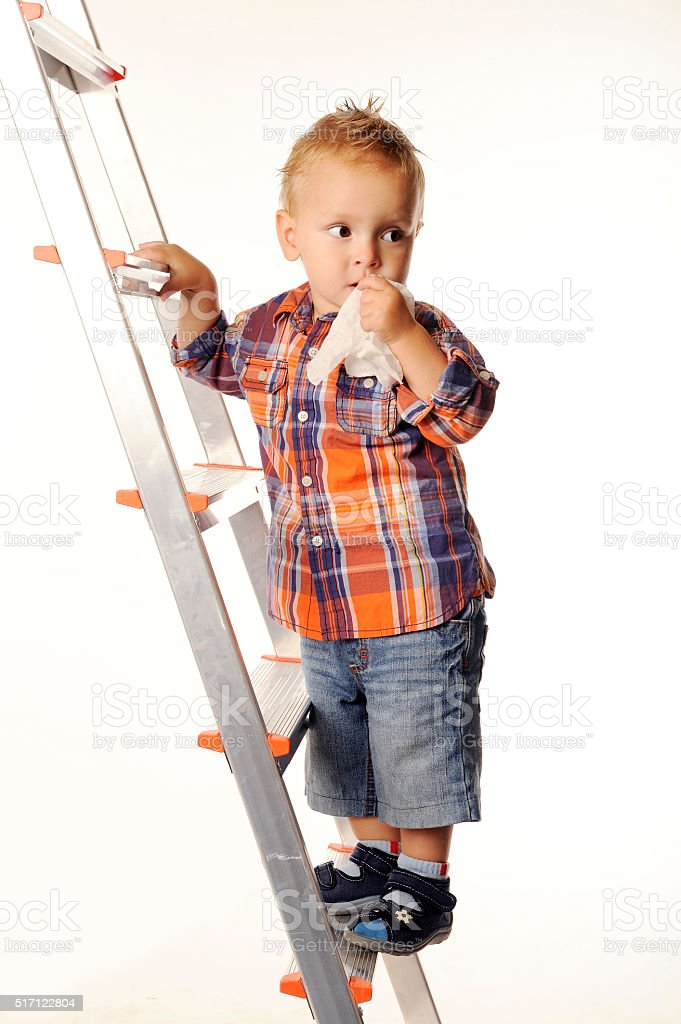 Three-year boy in checkered shirt and shorts on the stairs. stock photo