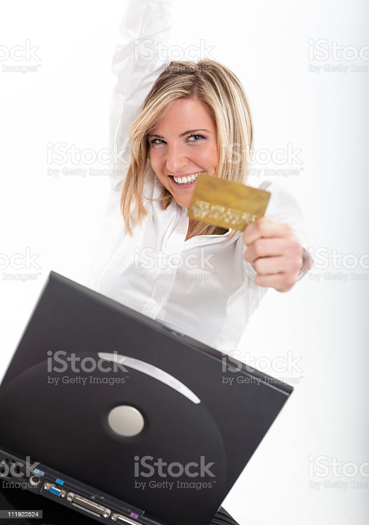 Thrilled young woman with  credit card and laptop stock photo