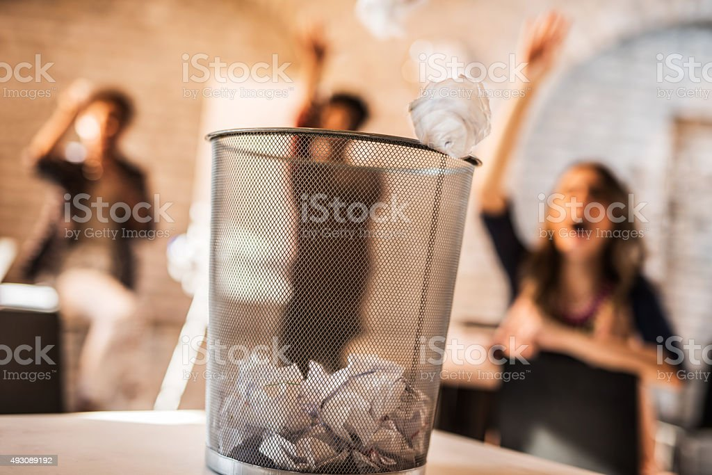 Throwing crumpled paper into a wastepaper basket. stock photo