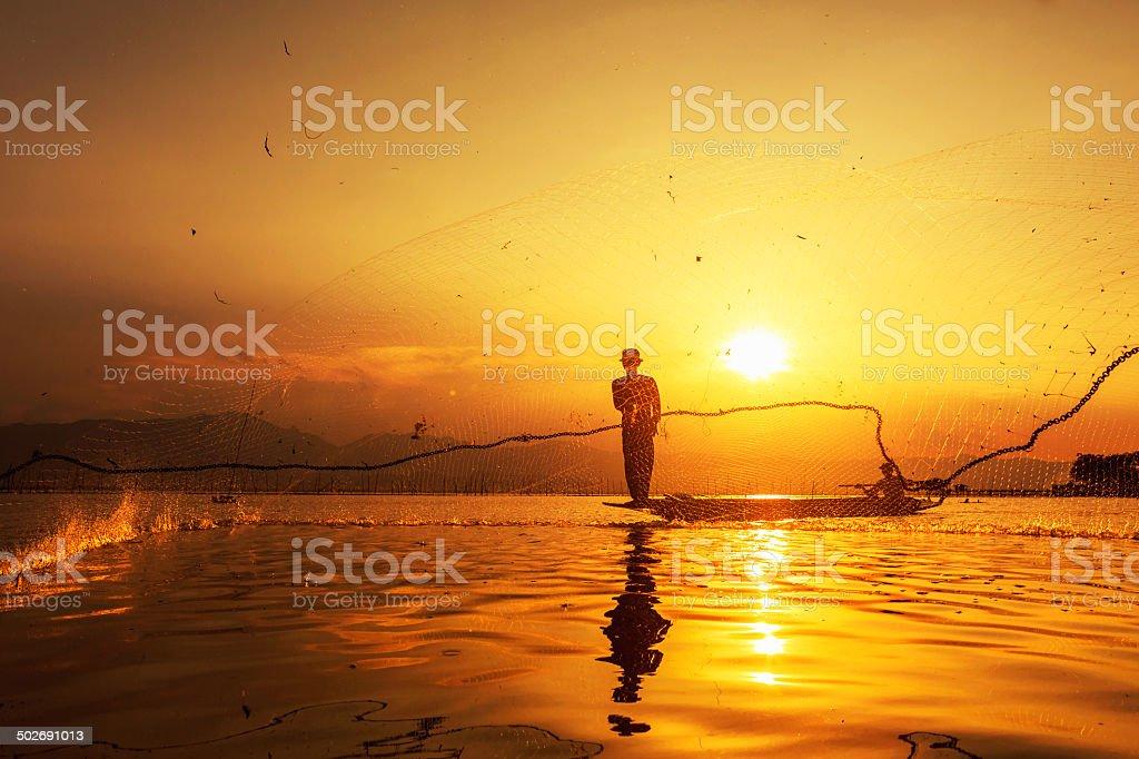 Werfen Fischnetz bei Sonnenuntergang Lizenzfreies stock-foto