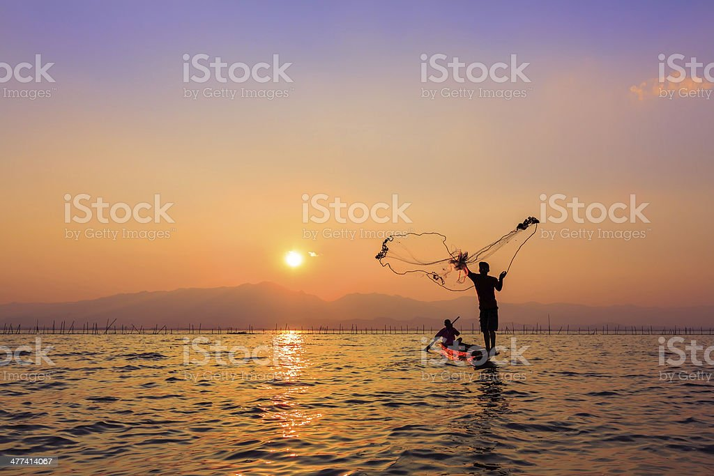 Werfen Fischnetz bei Sonnenuntergang, Thailand Lizenzfreies stock-foto