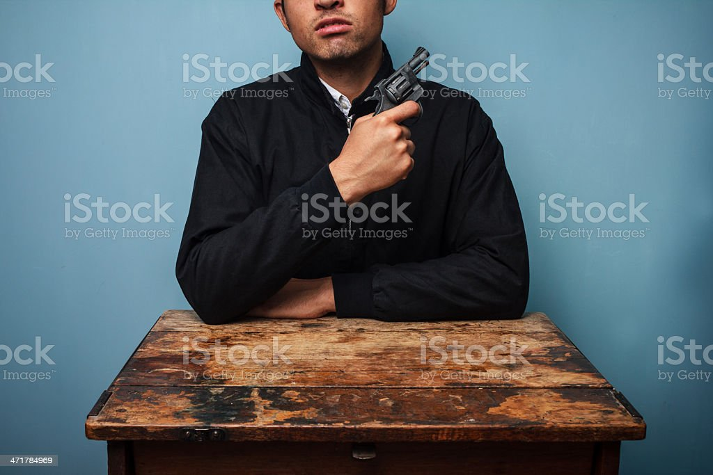Thug at table with gun and a mean look royalty-free stock photo
