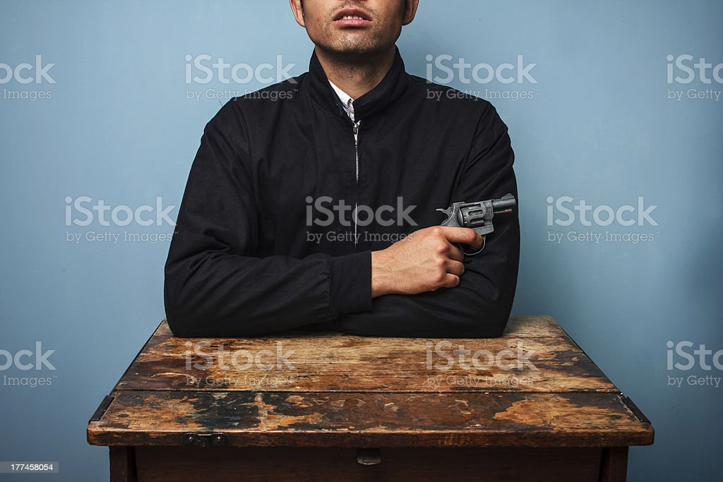 Thug at table with gun royalty-free stock photo
