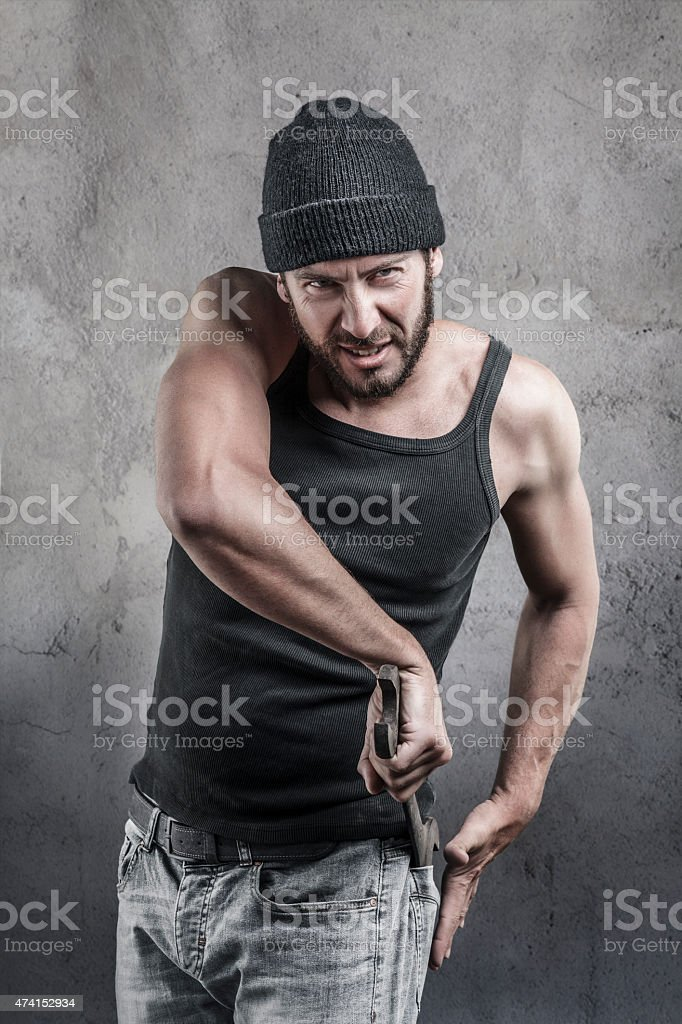 Thug preparing to use a wrench as a weapon stock photo
