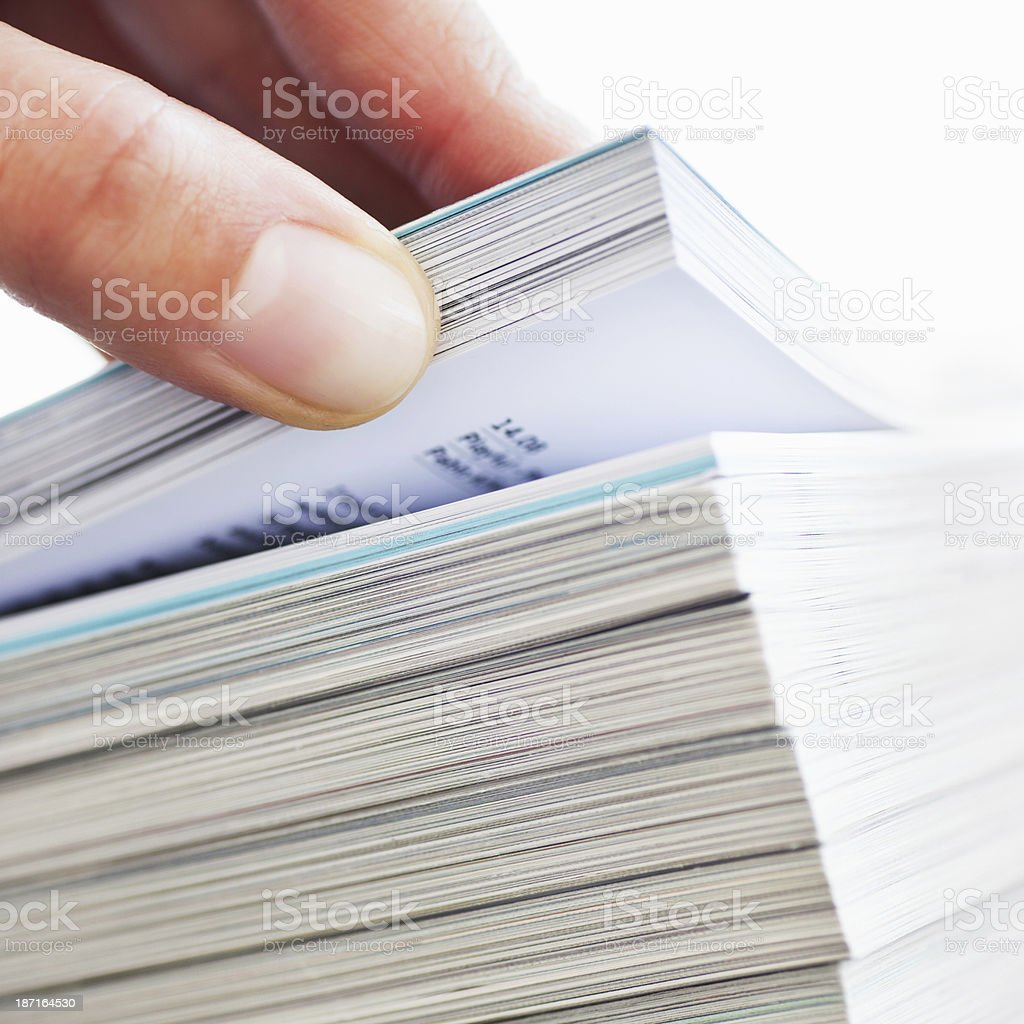 Thumb Browsing Through Stack of Magazines stock photo