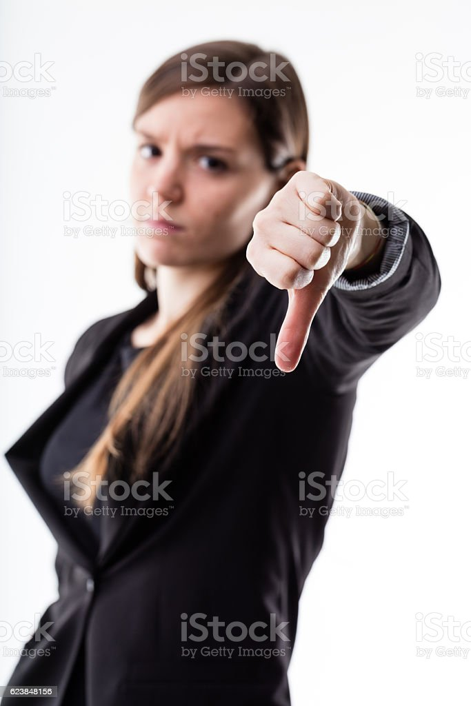 thumb down of a woman blurred in the background stock photo