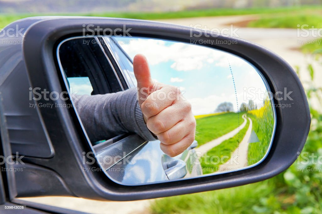 Thumb up in a side mirror stock photo