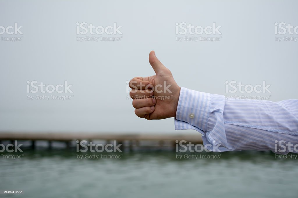 Thumb up. Man holding his arm straight holding thumb up stock photo